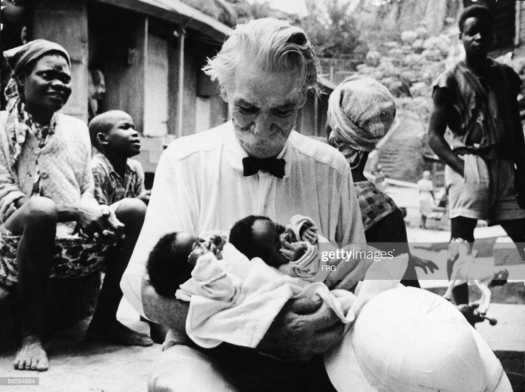 Albert Schweitzer Holds Two Newborn Infants At Lambarene : News Photo