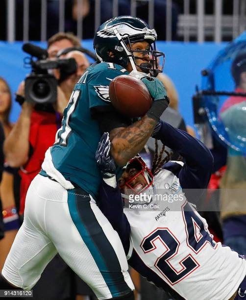 Alshon Jeffery of the Philadelphia Eagles bobbles the pass under pressure from Stephon Gilmore of the New England Patriots as teamamte Duron Harmon...