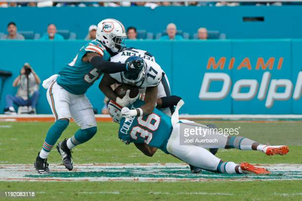 Alshon Jeffery of the Philadelphia Eagles is tackled by Jerome Baker and Adrian Colbert of the Miami Dolphins during an NFL game on December 1 2019...