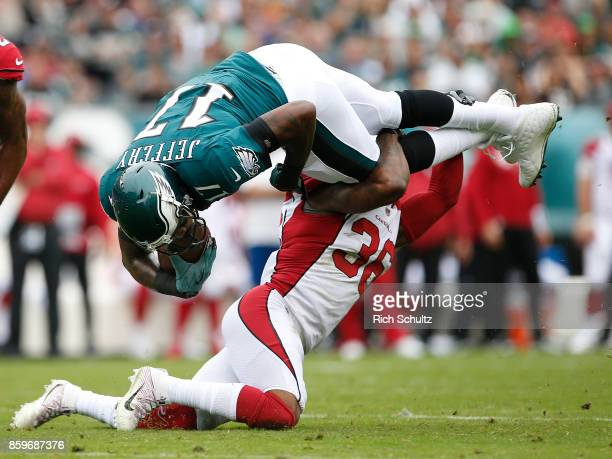 Alshon Jeffery of the Philadelphia Eagles is upended by Budda Baker of the Arizona Cardinals after making a catch for a first down during the first...