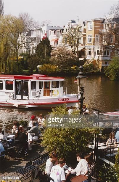 Alsterdampfer Susebek bei der Anfahrt an den Anleger Mühlenkamp in Hamburg Im Vordergrund das gut besuchte Café auf dem Anleger