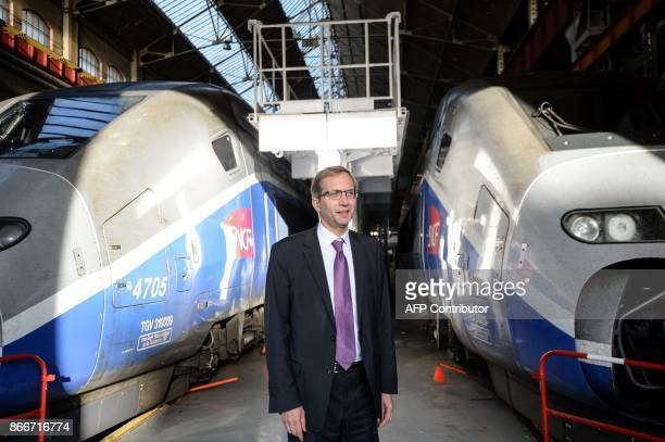 Alstom CIO Henri PoupartLafarge poses for photographers next to trains as he visits the site of French train maker Alstom in Belfort on October 26...