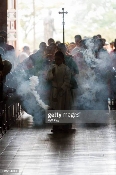 Altar boy with incense burner entering the church with parishioners