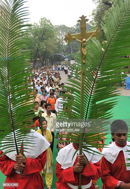 Altar boys hold palm leaves as they participate in Holy Mass at the Saint Mary's Church in Secunderabad the twin city of Hyderabad on March 28 on...