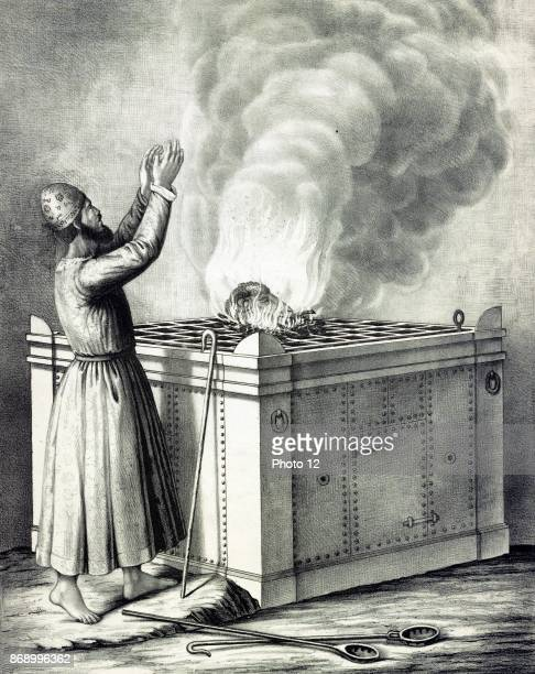 Altar of burnt offering Print shows a priest standing before a large altar with a grill on top on which a ram's head is being consumed by flames