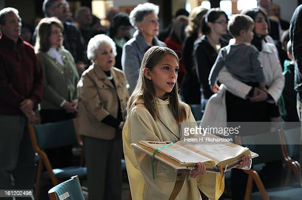 Altar server Joyce Bohn holds one of the new Roman Missals during Sunday Mass at Light of the World Roman Catholic Church in Littleton The church has...