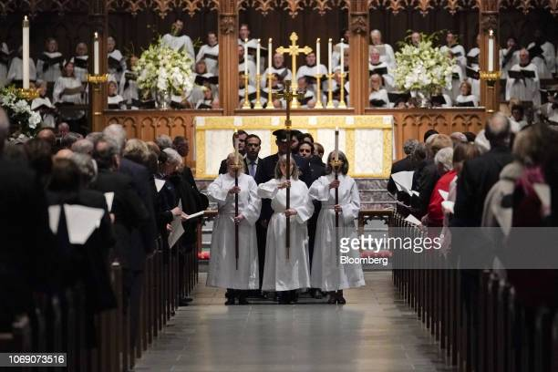 Altar servers carry a cross and lit candles exit following the conclusion of a funeral service for former President George HW Bush at St Martin's...