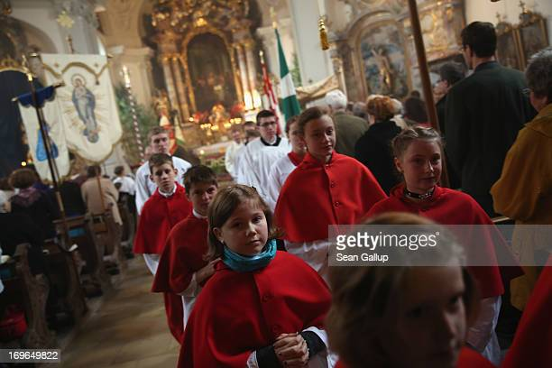 Altar servers follow a procession at the conclusion of the annual Corpus Christi mass at St Michael's Church on May 30 2013 in Seehausen am...