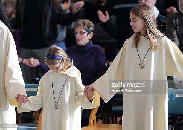 Altar servers Jacob Soderlin left Kaitlin Stanford 8 and Joyce Bohn right sing during Sunday Mass at Light of the World Roman Catholic Church in...