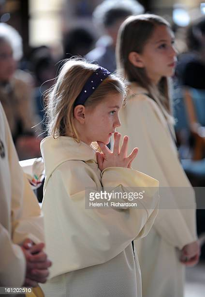 Altar servers Kaitlin Stanford middle and Joyce Bohn right pray during Sunday Mass at Light of the World Roman Catholic Church in Littleton The...