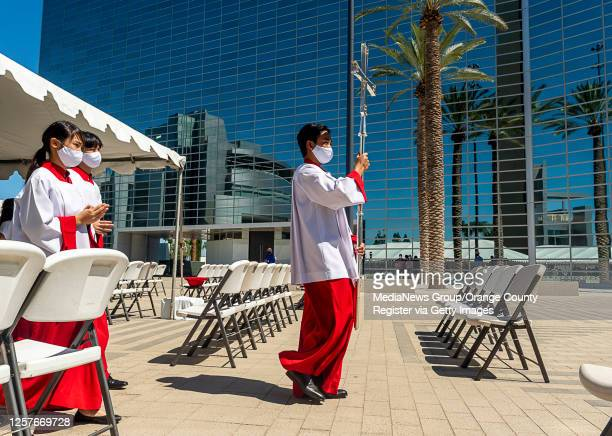 Altar servers move out from beneath a tent at the conclusion of an outdoor mass at Christ Cathedral in Garden Grove on Sunday, July 19, 2020....