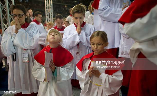 Altar servers pray during a mass given by Pope Benedict XVI at the Olympic stadium in Berlin on September 22 on the first day of his first state...