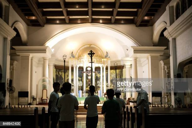 Altar servers rehearse their church duties at the San Roque Cathedral in Caloocan east of Manila on September 14 2017 Church bells were set to toll...