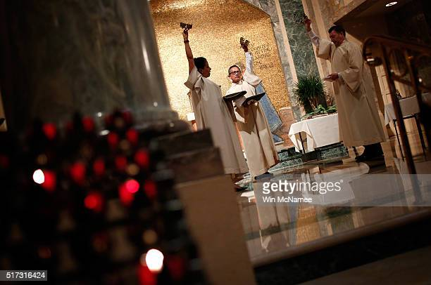 Altar servers ring bells during the start of the Mass of the Lord's Supper on Holy Thursday at the Cathedral of St Matthew the Apostle March 24 2016...
