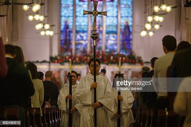 Altar servers walk down the aisle with candles and a cross after a Christingle service meaning 'Christ Light' at Hong Kong's St Paul's Cathedral...