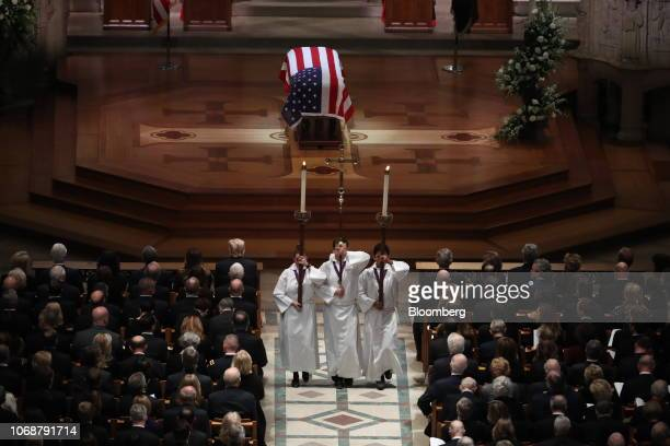 Altar servers walk in front of the flagdraped casket of former President George HW Bush during the end of a state funeral service at the National...