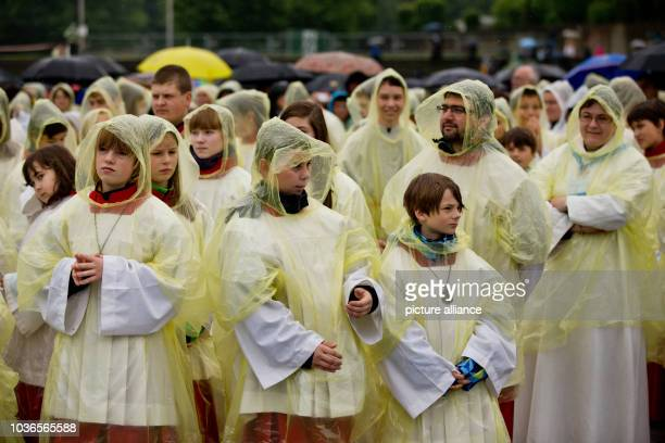 Altar servers wearing transparent raincoats against rain showers attend the Ascension mass at the 99th German Catholics Day in Regensburg Germany 29...