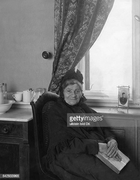Alte Frau mit Buch in einem 'Altersversorgungsheim' um 1902