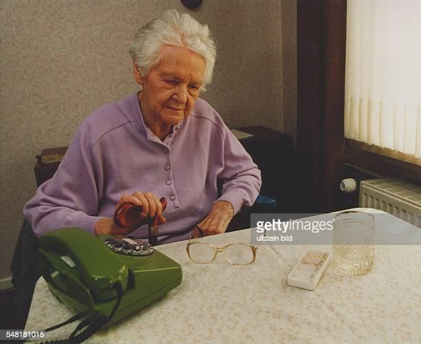 alte Frau sitzt am Tisch und wartet auf einen Anruf 1995