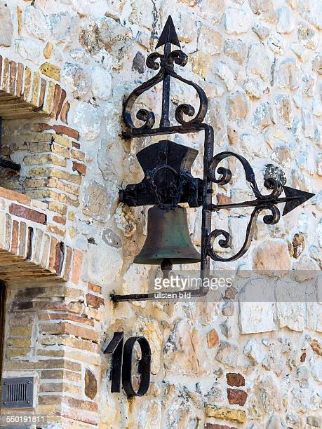 Alte Glocke an einer Hausmauer eines Steinhauses