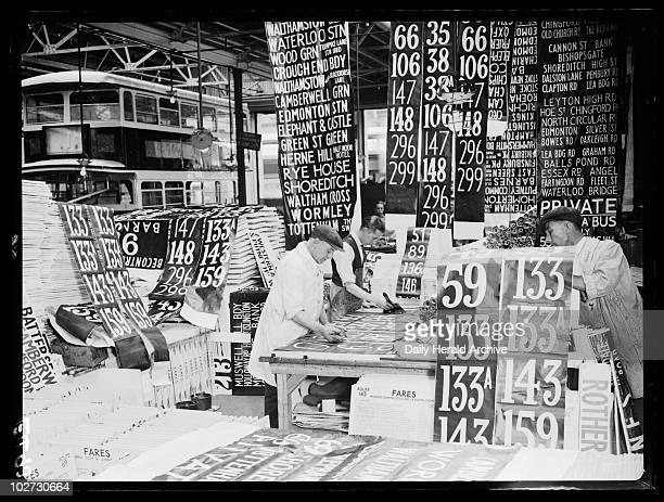 Altering bus route numbers 1934 A photograph of men altering bus route details in a London depot taken by Tomlin for the Daily Herald newspaper on 27...