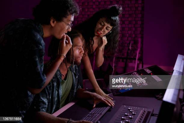 alternative band producing new album with african-american music producer in music studio - producer stock pictures, royalty-free photos & images