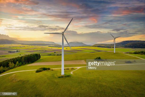 alternative energy wind turbine green landscape at sunset - wind power stock pictures, royalty-free photos & images