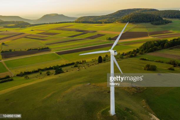alternative energy wind turbine in beautiful green landscape at sunset - wind power stock pictures, royalty-free photos & images
