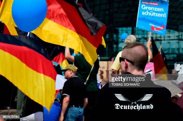 Alternative for Germany 's demonstrators holding AfD and German flags gather at the main station in Berlin to attend the demonstration for the future...