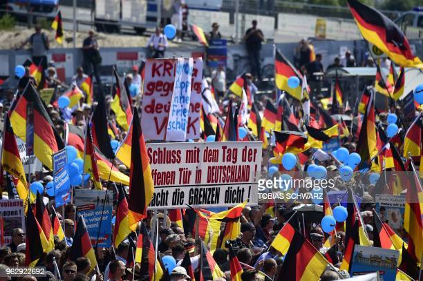 Alternative for Germany 's demonstrators holding placards reading end of the open doors in Germany close the borders gather at the main station in...