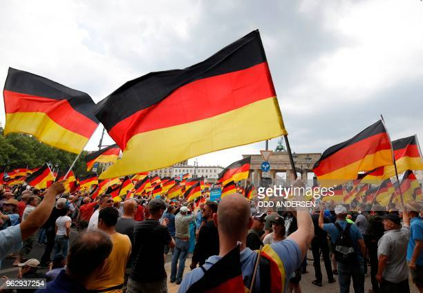 Alternative for Germany 's demonstrators wave German flags in front of the Brandenburg Gate in Berlin during the demonstration for the future of...