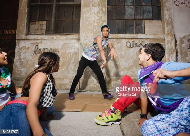 Alternative friends break dancing in urban setting