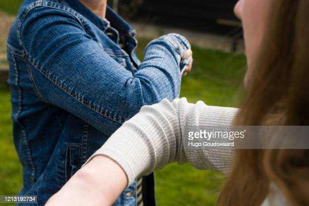 alternative handshake. bumping elbow to say hello. corona covid-19 meeting. - elbow bump stock pictures, royalty-free photos & images