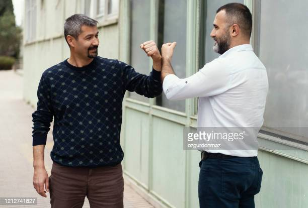 covid-19 alternative handshake. two people (male friends) bump elbows instead of hug or handshake. - elbow bump stock pictures, royalty-free photos & images