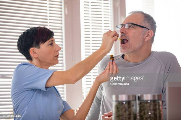 alternative healthcare worker dropping cbd oil on patient's tongue - cbd oil stock pictures, royalty-free photos & images
