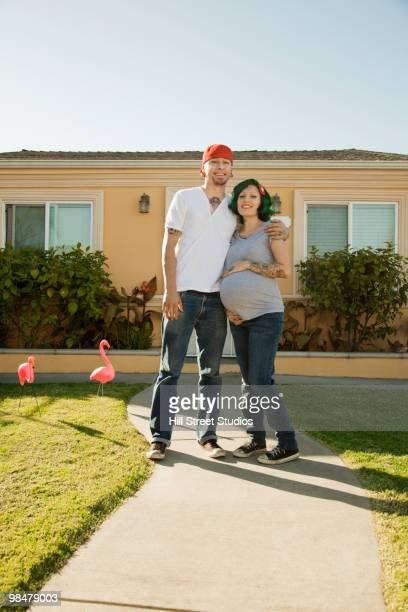 Alternative Hispanic couple standing in front of house
