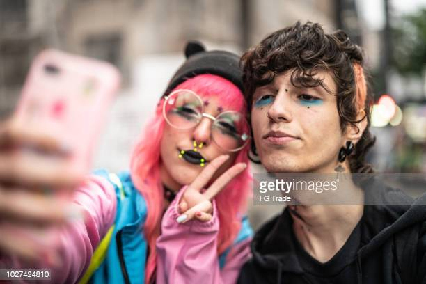 alternative lifestyle young couple taking a selfie - emo stock pictures, royalty-free photos & images