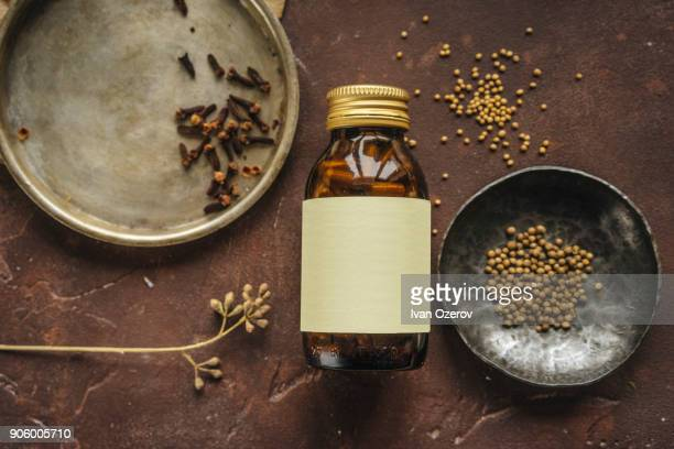 Alternative medicine jar with blank label near seeds