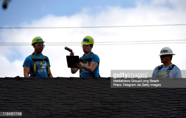 Alternatives professionals teaching students from University of Michigan how to install a rooftop solar systems at a home in Long Beach on Thursday...