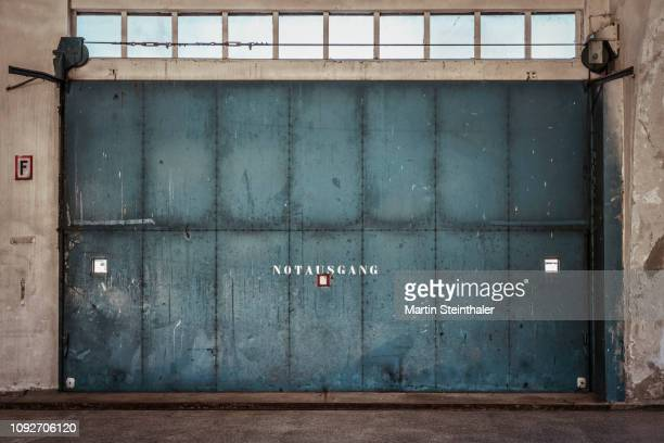 altes eisernes rolltor in fabrikshalle industrie - industrial door stock pictures, royalty-free photos & images
