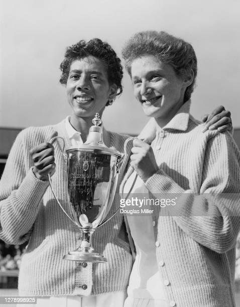 Althea Gibson of the United States and Angela Buxton of Great Britain hold the The Duchess of Kent Challenge Cup after defeating Fay Muller and...