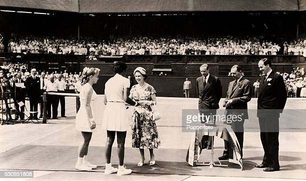 Althea Gibson of the United States the first black champion in the tournament's 80year history is congratulated by HM Queen Elizabeth II after...
