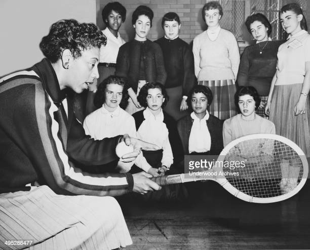 Althea Gibson US and Wimbledon tennis champion gives some pointers on the game to students attending a tennis clinic at Midwood High School in...