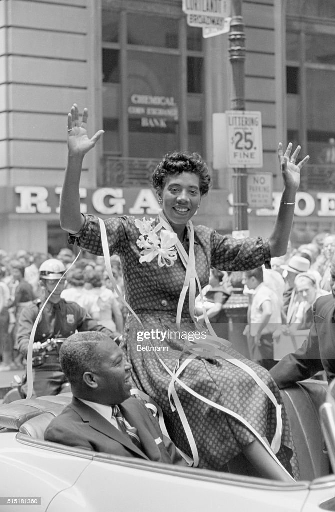Althea Gibson waves to crowds during a ticker-tape parade given in her honor after her victorious return from Wimbledon. Gibson was the first black woman to win the Wimbledon championship; she and Darlene Hard also won the women's doubles match. Beside Gibson is Hulan Jack, the first African American Borough President of Manhattan.