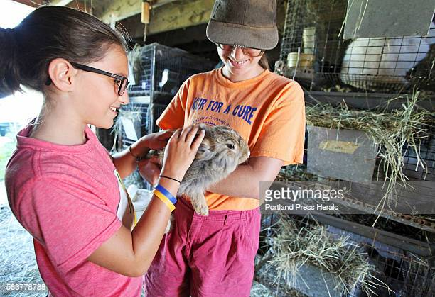 Althea McNulty of Falmouth feels the soft fur of an Angora rabbit held by Nancy Smith during Open Farm Day at Underhill Farm in Gorham