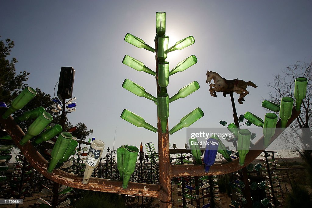Although collectors of bottles and other items found in the desert have all but gone by the wayside, Elmer Long carries on the tradition with his continual creation of a forest of ?bottle trees? on old Route 66 on June 15, 2007 near Oro Grande, California. Route 66 opened in 1926 to become an icon of American motoring freedom. It stretched from Chicago to Los Angeles and became a western migration route for people looking for work during the great depression of the 1930s or to escape the Dust Bowl disaster. Later it offered vacation getaways and driving adventures until 1985 when it was decommissioned as a federal highway. Today the motels, gas stations, and roadside attractions along the 'Mother Road' are disappearing at an alarming rate. Route 66 aficionados try to preserve some reminders of the by-gone era ? restoring some buildings, collecting memorabilia, and erecting thousands of new signs that read 'Route 66' - but most of the old landmarks are already in a state of decay or destroyed by vandals and neglect. Freeways, modern hotel chains, developer's projects, and even tourist attractions are blotting out the original reminders of the highway that inspired countless movies, books, and songs about life on the Western highway. Last week the National Trust for Historic Preservation included the old motels of Route 66 on its list of the 11 most endangered historic places.