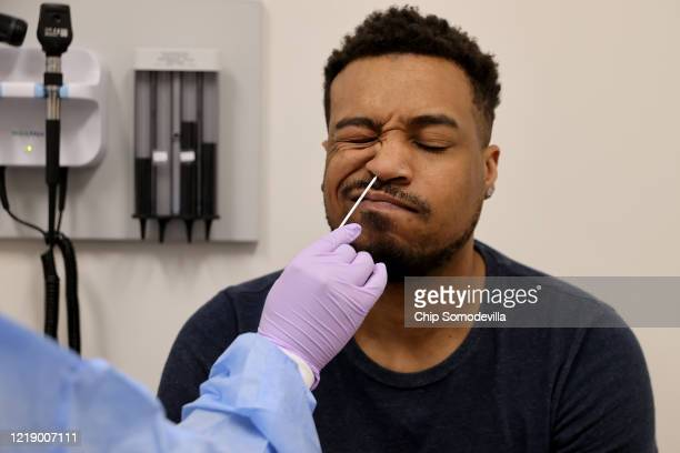 Although showing no symptoms and being cautious, Keith Whiteing has the back of his nasal passage swabbed while being tested for the novel...