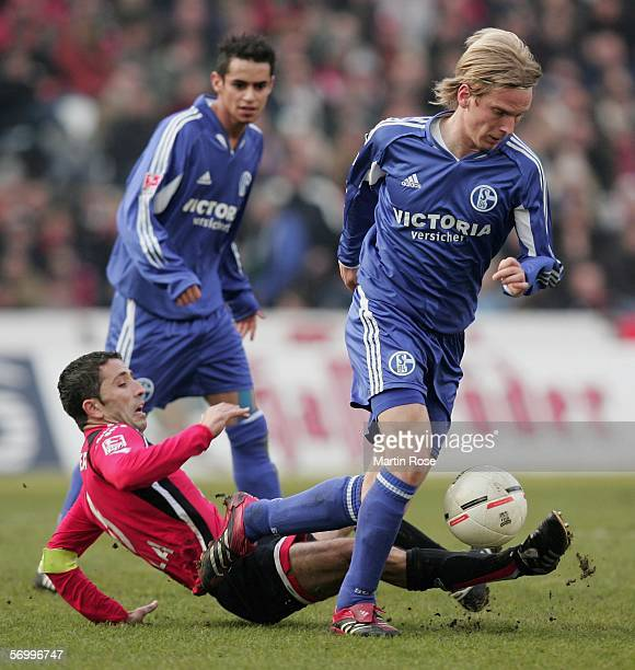 Altin Lala of Hannover challenges Christian Poulsen of Schalke for the ball during the Bundesliga match between Hanover 96 and FC Schalke 04 at the...