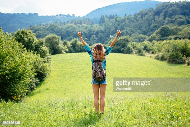 Alto Adige, back view of teenage girl with arms up standing on a meadow