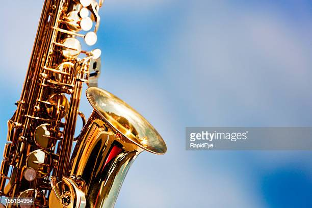 alto sax close up against sky with scattered clouds - saxophone stock pictures, royalty-free photos & images